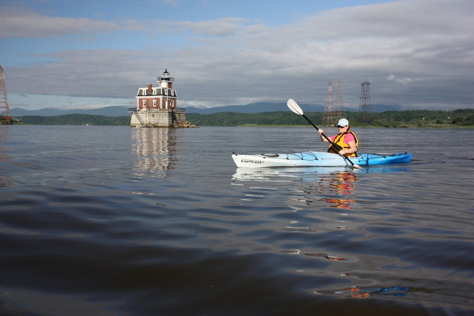 person kayaking in Greene County of NY near lighthouse