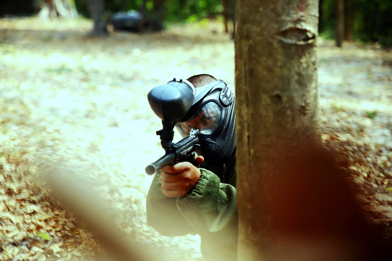 man hiding behind a tree while paintballing in the Catskills