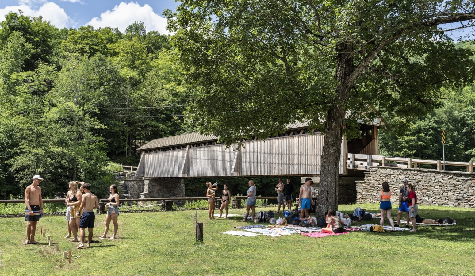 people enjoying summer day near covered bridge in the Catskills