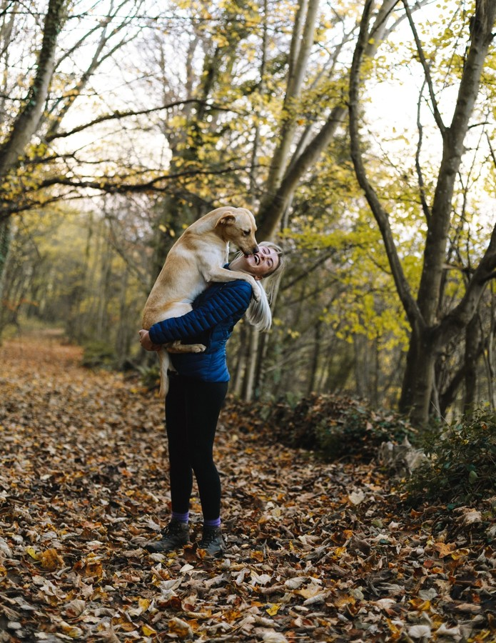 girl holding dog on a wooded trail