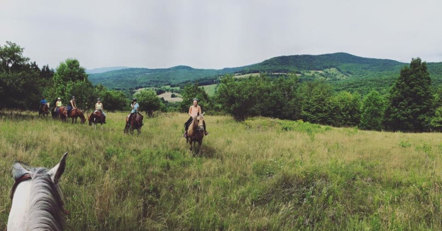group of people riding horses in the Catskills