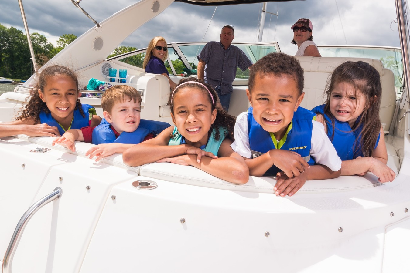 kids smiling from the back of boat