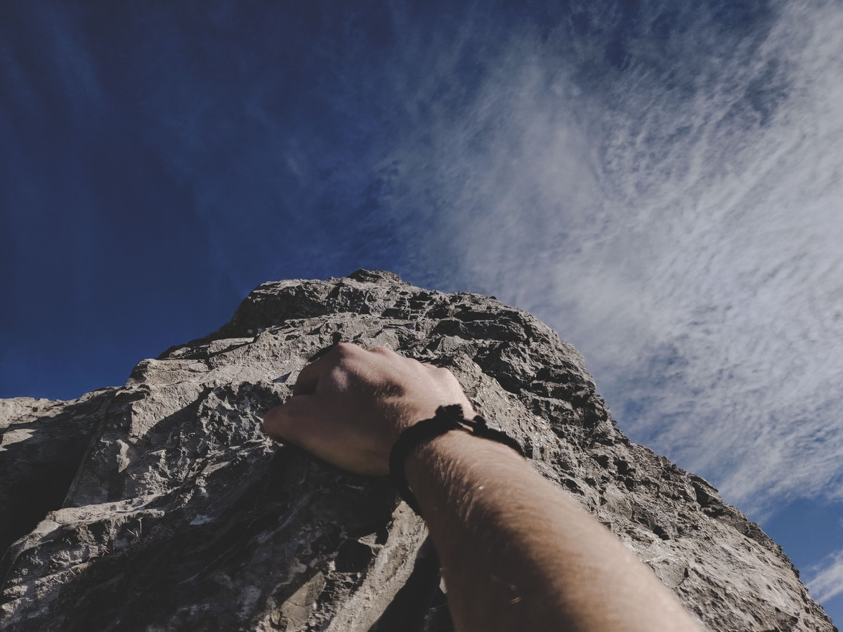 person rock climbing and reaching the top