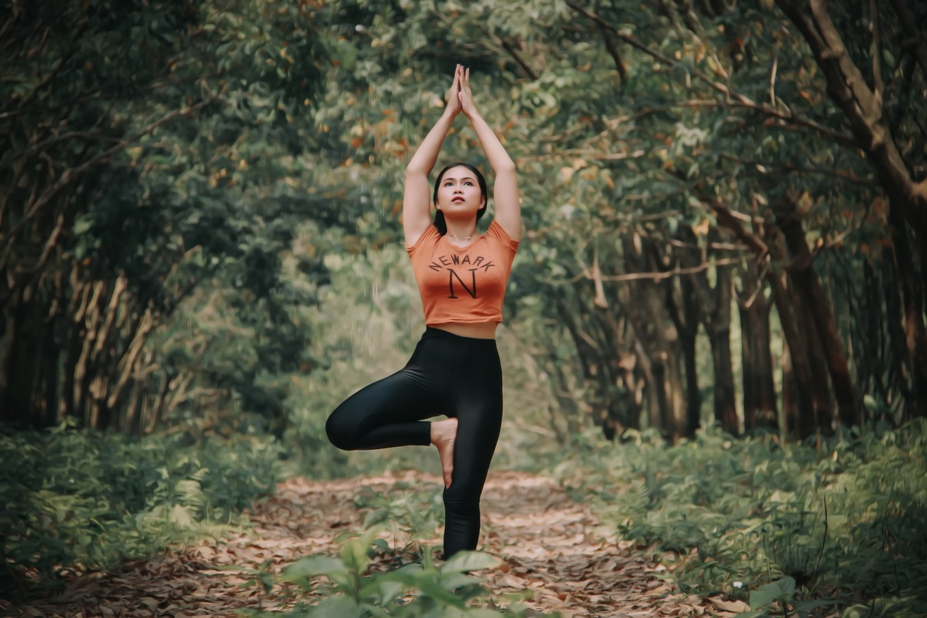 Woman practicing yoga in the woods